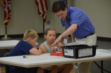 Dos alumnos y un profesor programando robots con Lego