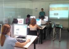 Imatge de la classe amb ordinadors i projector al fons