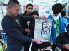 Joves de l'Òmnia Teb amb cartell de la Marató per la Pobresa