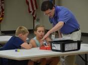 Dos alumnes i un professor programant robots amb Lego