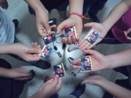 Mans de joves amb plaques de Micro:bit en un curs impartit per Colectic