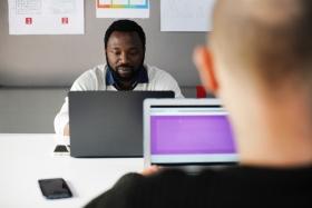 Dues persones treballant davant l'ordinador